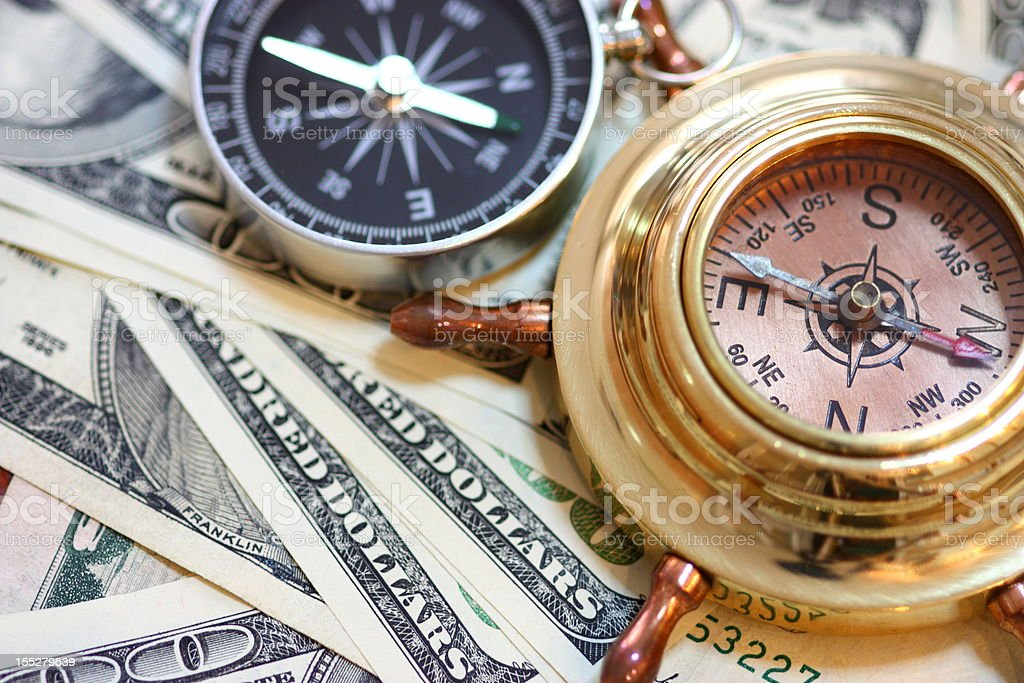 Nautical compasses on top of US paper currency stock photo