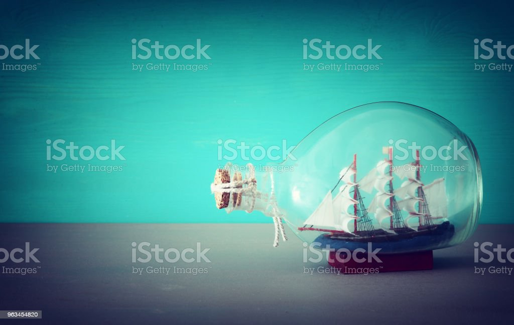 nautical concept image with sail boat in the bottle over wooden table. Selective focus. - Zbiór zdjęć royalty-free (Antyczny)