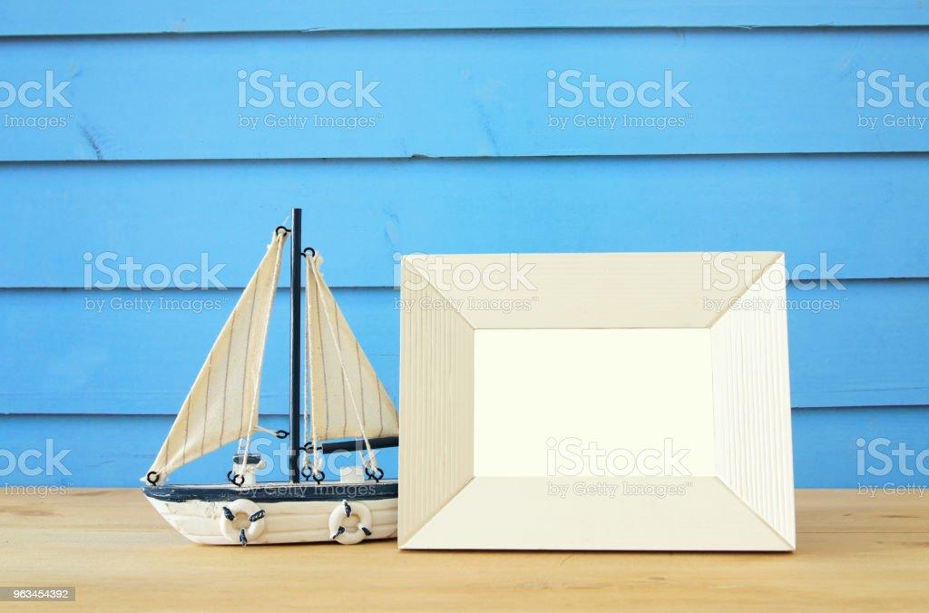 Ahşap masa üzerinde boş fotoğraf çerçevesi ve yelken teknesi ile deniz kavramı. Fotoğraf montaj için. - Royalty-free Ahşap Stok görsel