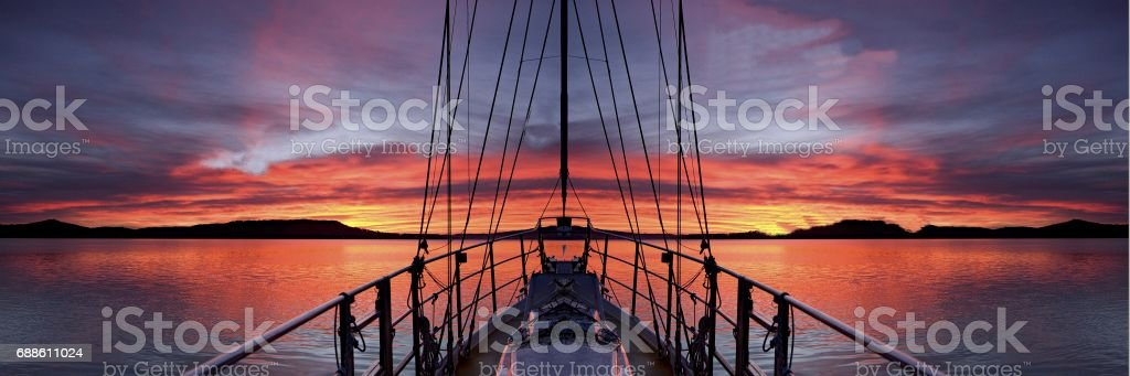 Nautical Crimson  Sunrise with Boat and water reflections. stock photo