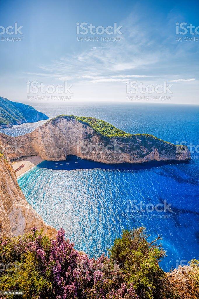 Navagio beach with shipwreck on Zakynthos island in Greece Navagio beach with shipwreck and flowers on Zakynthos island in Greece Bay of Water Stock Photo