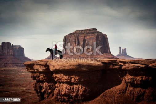 Subject: A native American Indian cowboy on a horse over a cliff looking into the distance.
