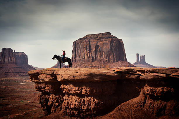 Navajo Cowboy in American Southwest Landscape Subject: A native American Indian cowboy on a horse over a cliff looking into the distance. desaturated stock pictures, royalty-free photos & images