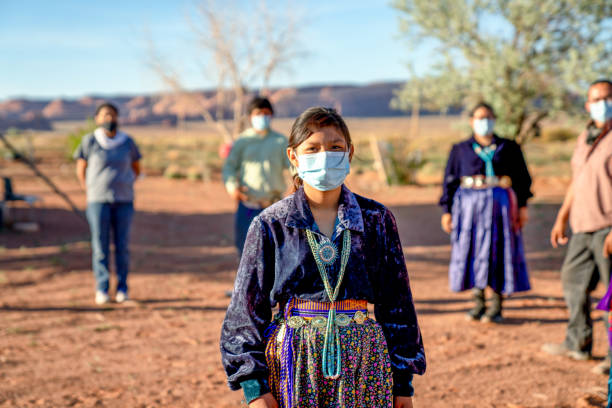 A Navajo Family Practicing Social Distancing, Wearing Masks During The Coronavirus Pandemic American indigenous family aware of the dangers of the Covid19 pandemic stands 6 feet apart from one another indigenous peoples of the americas stock pictures, royalty-free photos & images