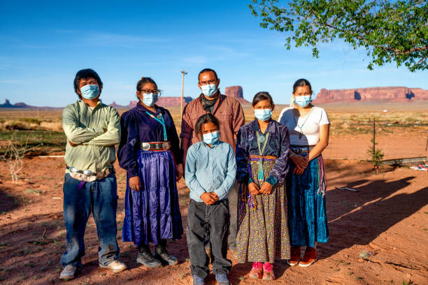 Navajo Family Social Distancing with Covid-19 Masks outside their home in Monument Valley Arizona stock photo