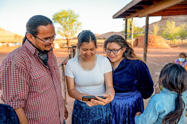 Navajo Family Spending Time Sharing Photos from a Smart Phone stock photo