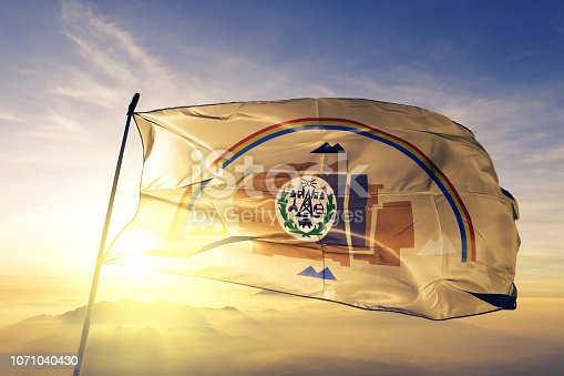 Navajo flag on flagpole textile cloth fabric waving on the top sunrise mist fog