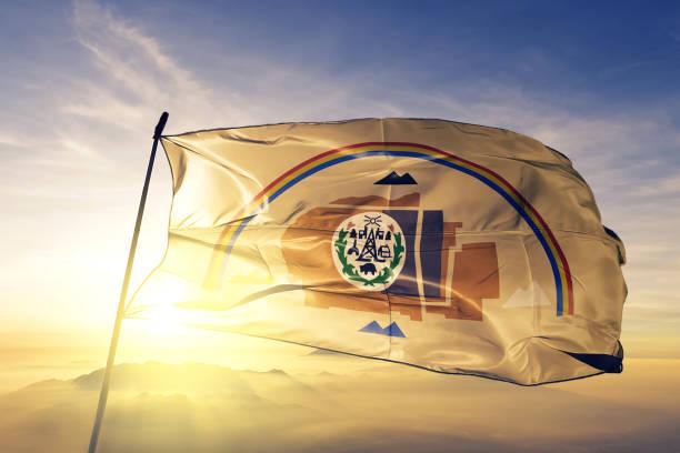 Navajo flag textile cloth fabric waving on the top sunrise mist fog stock photo