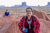 Navajo Grandmother and Granddaughter posing together in front of The Mittens Rock Formations in the Monument Valley Tribal Park in Arizona