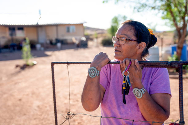A Navajo Grandmother Standing By The Gate Of Her Home In Monument Valley, Arizona, Coronavirus stock photo