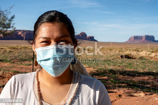 A teenage Navajo girl wears a mask for protection from Coronavirus stands on her family property in Monument Valley Tribal Park