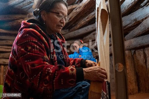 A native American woman weaves a saddle blanket while her mother weaves a basket in the background