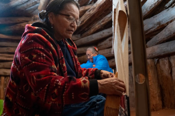 A Navajo Woman Weaves A Saddle Blanket On A Loom, Her Mother In The Background stock photo