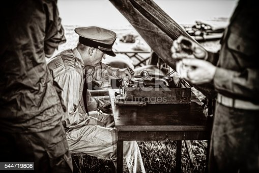 A Naval Officer in the field.  He is set up in a make shift tent along with his old vintage photograph to keep him company.  He is whistling to the tune the record is playing.  Some Grain and blur for movement.  He is flanked on either side by WWII US Infantrymen.