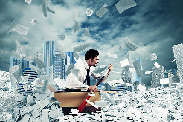 Navigate the bureaucracy Concept of bureaucracy with man paddling in a sea of sheets bureaucracy stock pictures, royalty-free photos & images