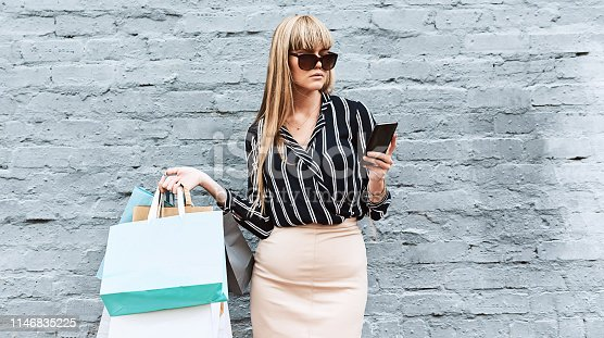 Shot of a beautiful and stylish young woman using a smartphone while shopping in the city