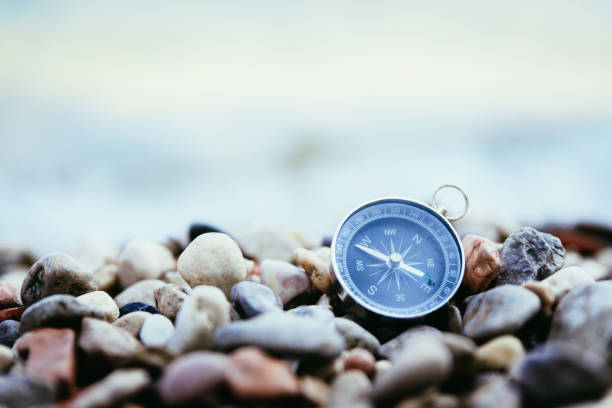 Navigation concept: Compass is lying on the beach near the sea Compass on the beach, small stones, text space navigational equipment stock pictures, royalty-free photos & images