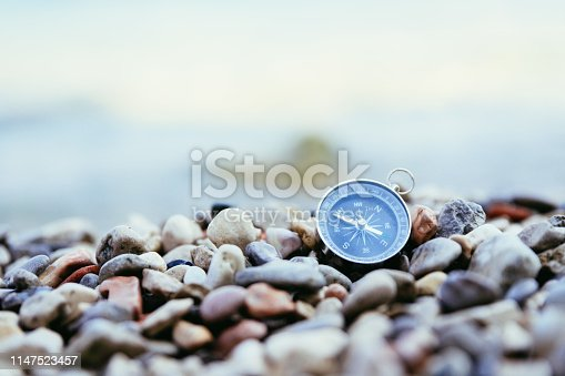 Compass on the beach, small stones, text space
