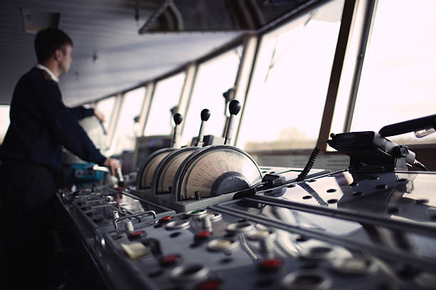 Navigation officer driving ship on the river. stock photo