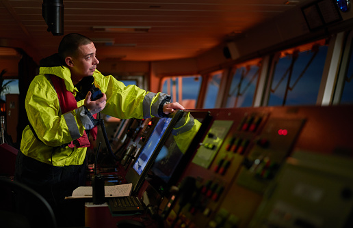 Navigator. pilot, captain as part of ship crew performing daily duties with VHF radio, binoculars on board of modern ship with high quality navigation equipment on the bridge on sunrise.