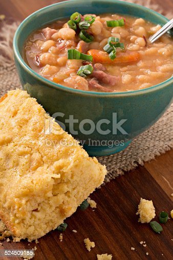 A high angle extreme close up shot of a turquoise bowl full of hearty navy bean soup choke full of beans, ham and ham hock meat. the soup is garnished with some green scallions. A slice of freshly baked cornbread lays next to the bowl on the burlap place mat.