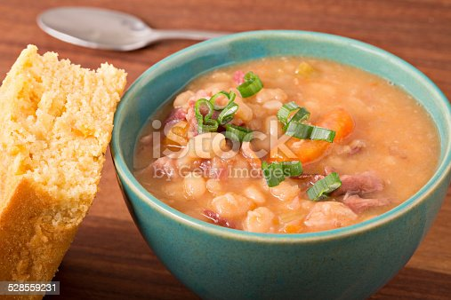 A high angle extreme close up horizontal photograph of a turquoise bowl full of hearty navy bean soup garnished with chopped green scallions and choke full of beans, ham, carrots and other vegetables swimming in a thick broth. A slice of freshly baked yellow cornbread leans against the bowl and there is a metal spoon in the background.