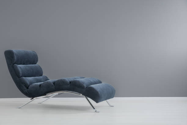 Navy blue chaise lounge Navy blue chaise lounge with metallic elements in spacious apartment chaise longue stock pictures, royalty-free photos & images