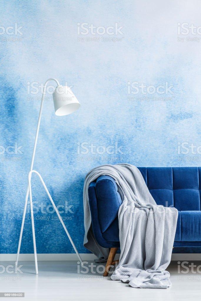 Photo libre de droit de Canapé Bleu Marine Avec Couverture Gris Et Blanc  Lampadaire Contre Mur Ombre Bleue Et Blanche Dans Un Salon Intérieur Vraie  ...