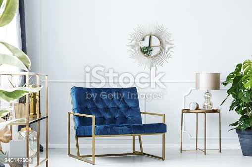 Navy blue armchair next to gold table with lamp against white wall with mirror in living room interior