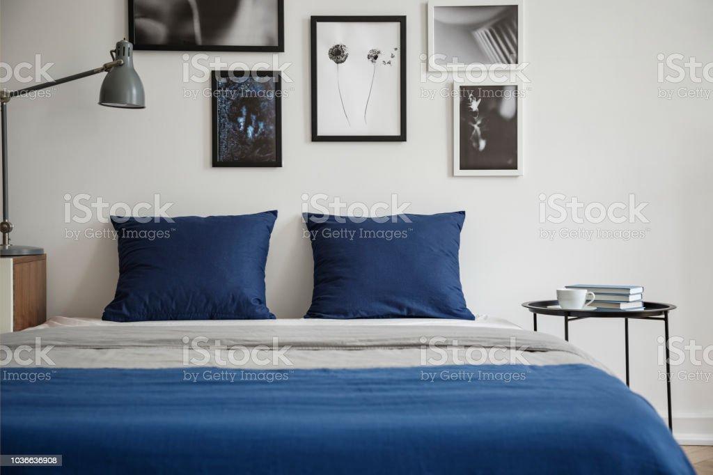 Marineblaue Kissen Auf Bett Zwischen Tisch Und Lampe Innen Weisse Schlafzimmer Mit Plakaten Echtes Foto Stockfoto Und Mehr Bilder Von Bett Istock