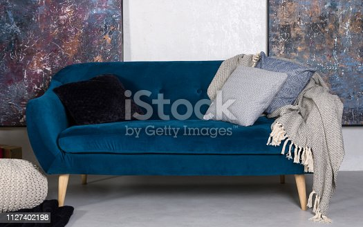 Navy blue retro sofa bed with cushions and gray blanket