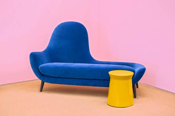 navy blue sofa on a pink background, laconic interior - поп арт стоковые фото и изображения