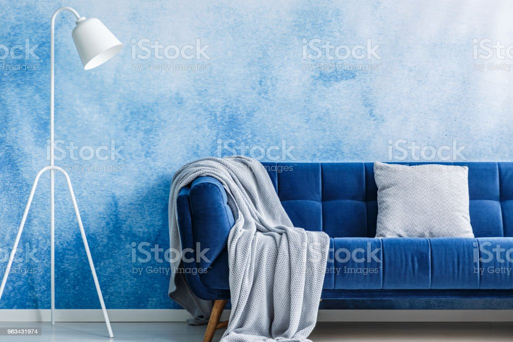 Canapé bleu marine avec couverture et oreiller, lampe mis sur un mur d'ombre dans un intérieur de salon - Photo de Ameublement libre de droits