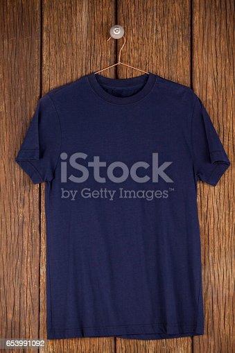 Navy blue t-shirt on hanger on wood panelling