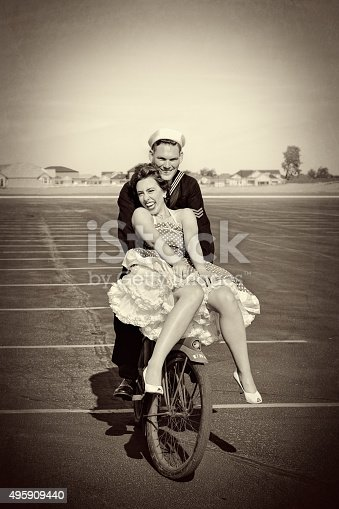 WWII Navy Man and His Pretty Woman Riding A Bike. They are laughing and having fun as she tries to keep her dress from blowing up in the wind.  Warm, happy and iconic.  Some Grain.