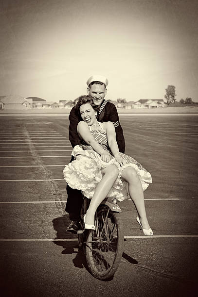 wwii navy man and his pretty woman riding a bike - world war ii stock photos and pictures
