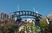 In Chicago, USA along the side walk on the Navy Pier is an entrance to the Beer Garden marked with signage and landscaped flowers on a warm, autumn day.