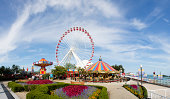 Chicago, USA - September 3rd, 2013: Fairground with swing ride, carousel and Ferris Wheel at Navy Pier in Chicago. Navy Pier is one of Chicago's main tourist attractions with amusement park. People can be seen walking around the park.