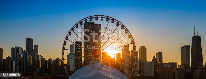 The sun sets behind the Navy Pier Ferris Wheel in Chicago, Illinois.
