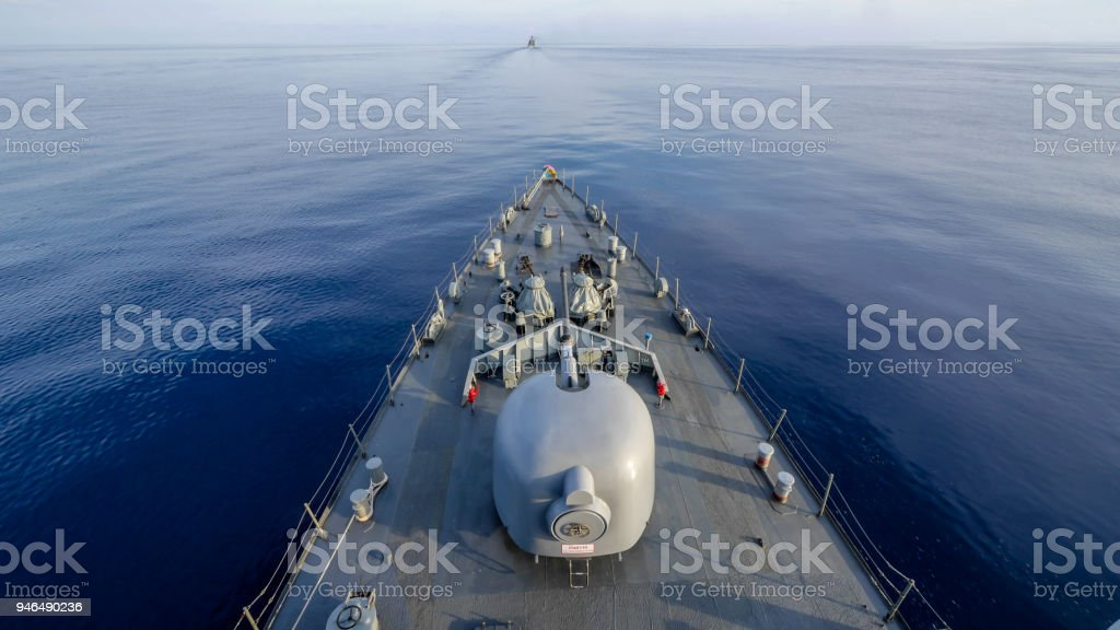 Navy ship sailing along the calm sea ,view from bow. The phase behind gun turret is Thai language it's a caution for operators mean 'Caution Gun may turn without any notice' stock photo