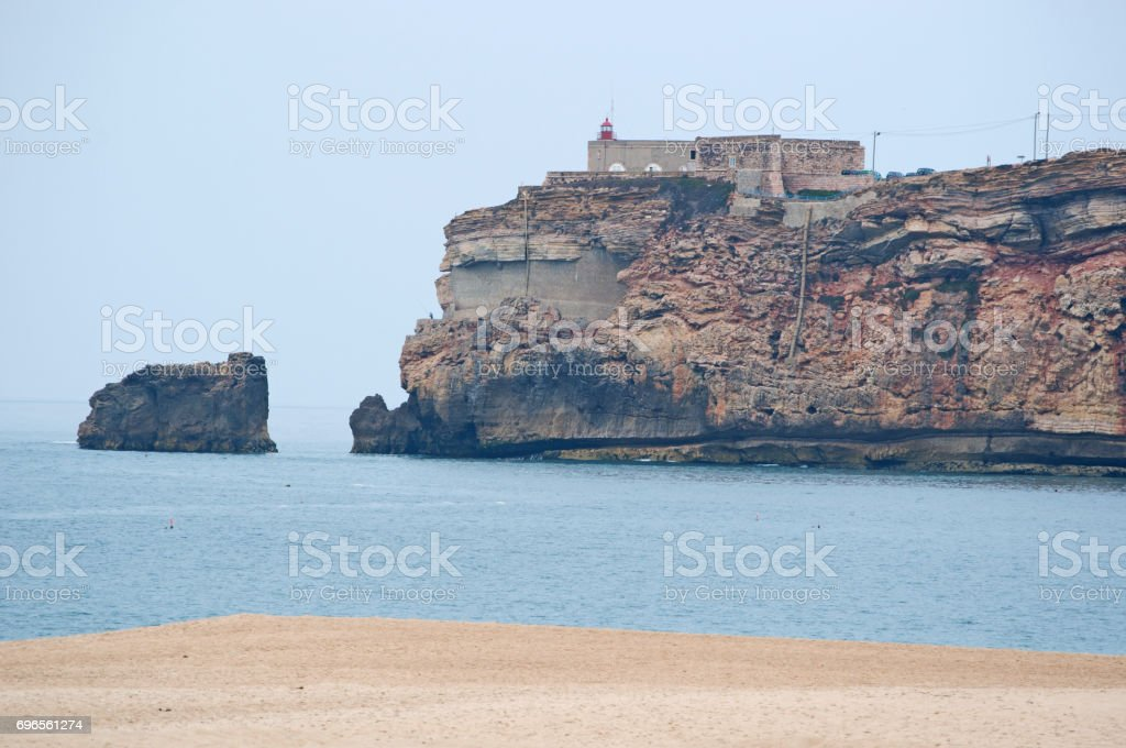 Nazaré: view of the beach of Sitio, the old neighborhood of the town of Nazaré perched on a cliff, and the lighthouse stock photo