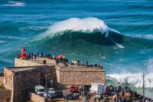 Nazare, Portugal, Surfer Riding Huge Wave Near the Fort of Nazare Lighthouse stock photo