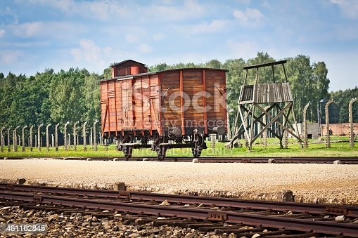 Auschwitz - Birkenau, Poland - August 20 2010:The Freight truck on the railway platform where prisoners were brought during World War II. The barbed wire electrical fence with the guard's watch tower in background, Auschwitz - Birkenau, concentration camp, Poland