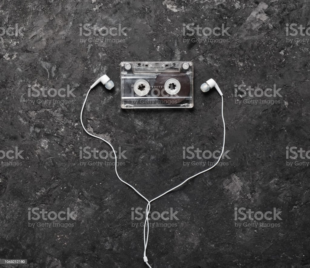 nceptual photo illustrating the love of music. Audio cassette and headphones on a black concrete background. Top view. – zdjęcie