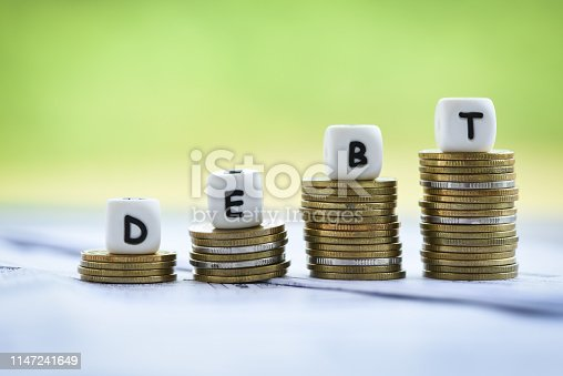 Debt dices on money coin stack staircase step up / Increased liabilities from exemption debt consolidation concept of financial crisis and problems risk business management loan interest