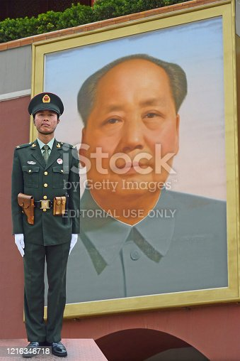 Beijing, China - 3 May, 2011: A soldier stands guard in front of the Palace Museum with Mao Zedong portrait in background. The collections of the Palace Museum are well protected and are based on Qing imperial.