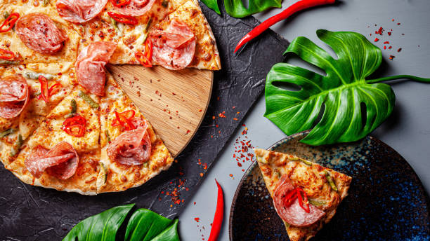 Neapolitan, Mexican cuisine. Pizza with salami sausage, with red pepper, jalapenos, pickled cucumbers and tomato pilati sauce. background image, copy space text
