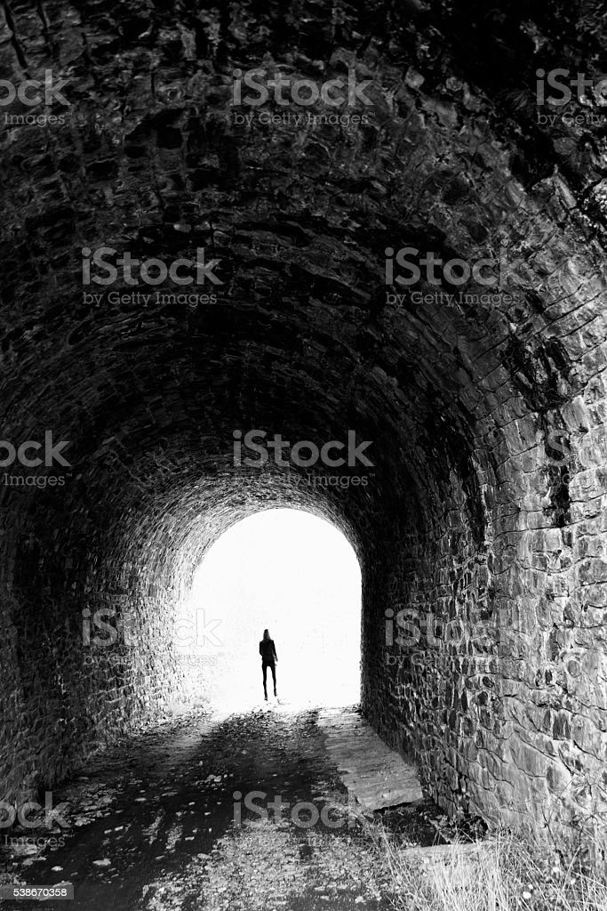 Near death experience : woman coming out of the tunnel stock photo