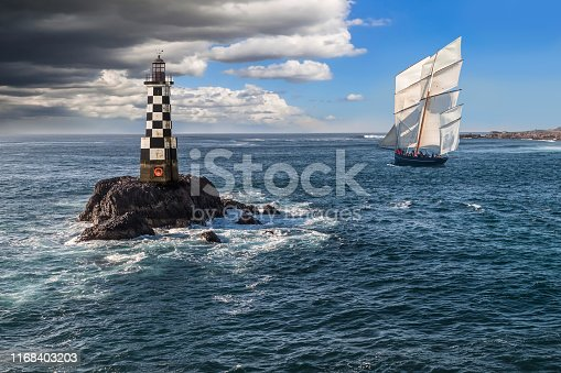 Sailboat Close to the Shore and Next to a Lighthouse with a Storm Coming