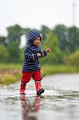 nearly 2 years old girl having fun outdoors in rain